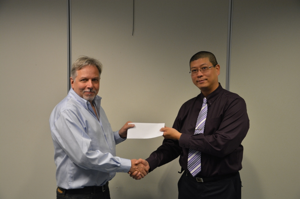 Nigel Cornwall (left) accepting a cheque from David Chen (right) on behalf of the Barnet Rifle Club